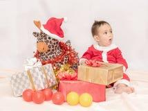 Uma criança no terno vermelho de Santa Claus que senta-se com boneca amo da rena Foto de Stock