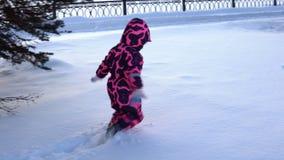 Uma criança nos macacões anda através dos montes de neve video estoque