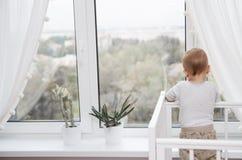 Uma criança olha para fora a janela Fotografia de Stock