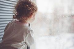 Uma criança olha para fora a janela. fotos de stock royalty free