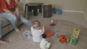 Uma criança pequena é jogada no assoalho com brinquedos e os pais são ocupados com seus próprios casos Família em casa video estoque