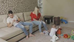 Uma criança pequena é jogada no assoalho com brinquedos e os pais são ocupados com seus próprios casos Família em casa filme