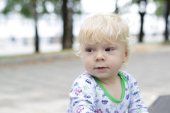 Uma criança pequena aprende andar perto dos bancos, criança Foto de Stock
