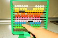 Uma criança pequena aprende a matemática no ábaco foto de stock
