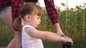 Uma criança pequena aprende montar uma bicicleta A mamã ensina a filha montar uma bicicleta Jogos da mãe com sua filha pequena E