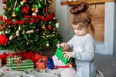 Uma criança pequena desembala o presente O conceito do Natal e do sim novo fotografia de stock royalty free