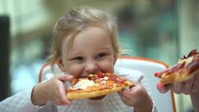 Uma criança pequena em um café do fast food come a pizza Comer engraçado do retrato bonito das meninas da criança na corte de fas filme