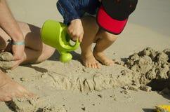 Uma criança pequena em um tampão derrama a água da lata molhando fotos de stock