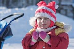 Uma criança pequena está bebendo uma bebida quente no inverno fotografia de stock royalty free