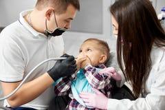 Uma criança pequena está cobrindo sua boca que é assustado devido ao tratamento dental realizado por um dentista masculino imagem de stock