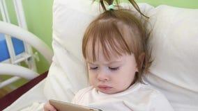 Uma criança pequena está olhando desenhos animados em um smartphone criança que joga no telefone na cama Menina que joga com uma  video estoque