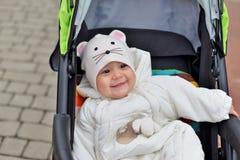 Uma criança pequena nos macacões que sentam-se na cadeira de rodas e no sorriso imagem de stock royalty free