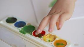 Uma criança pequena pinta com a aquarela, molhando seu dedo em um frasco da pintura video estoque