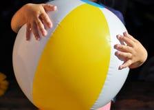 Uma criança pequena que guarda uma bola inflável com uma listra amarela em uma caminhada no jardim fotografia de stock royalty free