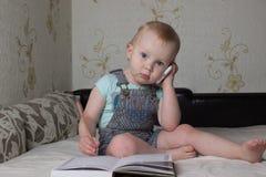 Uma criança pequena que senta-se no sofá e que escreve em um caderno o punho está no telefone Fotografia de Stock