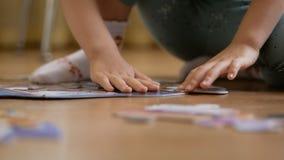 Uma criança pequena, recolhendo os enigmas que sentam-se no assoalho na sala Close-up das mãos da criança vídeos de arquivo