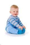Uma criança pequena senta-se e é jogada imagens de stock