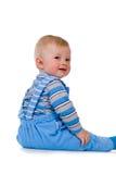 Uma criança pequena senta-se e ri-se imagens de stock royalty free