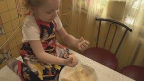 Uma criança pequena senta-se na tabela e amassa-se a massa vídeos de arquivo