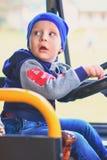 Uma criança pequena senta-se no táxi do ônibus atrás da roda e olha-se para trás Retrato vertical imagem de stock royalty free