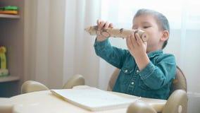 Uma criança pequena tira um lápis muito grande filme