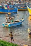 Uma criança perto dos barcos de madeira no porto Fotografia de Stock Royalty Free