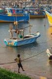 Uma criança perto dos barcos de madeira no porto Foto de Stock