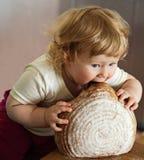 Uma criança que come o pão grande Fotografia de Stock