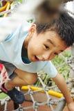 Uma criança que escala uma ginástica da selva. Fotografia de Stock Royalty Free