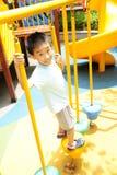 Uma criança que escala uma ginástica da selva. fotos de stock royalty free