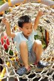 Uma criança que escala uma ginástica da selva. fotografia de stock