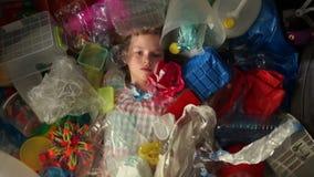 Uma criança que a estudante se está encontrando em uma pilha do lixo multi-colorido, um saco de plástico cai sobre ela O problema video estoque