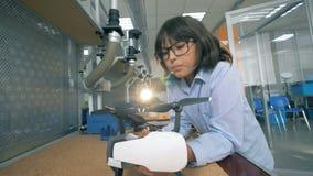 Uma criança que fixa um zangão em um laboratório, fim acima filme