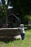 Uma criança que joga fora com um utensílio molhando fotografia de stock