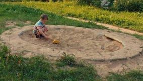 Uma criança que joga na caixa de areia video estoque