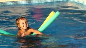 Uma criança que joga na piscina, com som video estoque