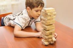Uma criança que joga o jogo da pilha dos blocos de madeira Imagem de Stock Royalty Free