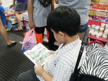 uma criança que lê um livro dos desenhos animados na feira de livro em Banguecoque Fotografia de Stock