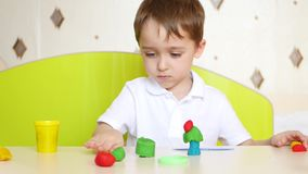 Uma criança que senta-se na tabela, em jogos em esculturas coloridas do plasticine ou em massa para jogos vídeos de arquivo