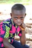 Uma criança que senta serenely a venda do creu Imagens de Stock