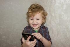 Uma criança satisfeita está feliz que esteve permitido jogar com seu smartphone dos parent's imagem de stock