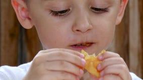 Uma criança senta-se em uma tabela na perspectiva de uma parede de madeira e come-se microplaquetas Close up do bebê da boca vídeos de arquivo