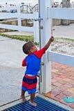 Uma criança tenta regar fora em um chuveiro exterior na praia Fotografia de Stock Royalty Free