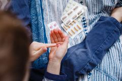 Uma criança tentada a tomar medicinas sem pais O menino guarda muitos comprimidos azuis disponível e tentou-os tomá-los Situação  fotos de stock royalty free