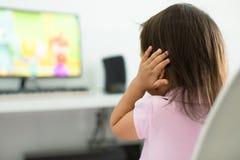 Uma criança terrificada, receosa dos sons altos da televisão autism imagem de stock royalty free