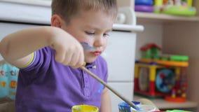 Uma criança tira com pinturas coloridas ao sentar-se na tabela video estoque