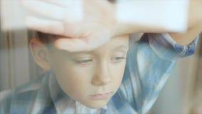 Uma criança triste olha para fora a janela vídeos de arquivo