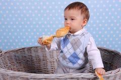 Uma crian?a min?scula come um bolo seco em uma cesta tecida de uma ?rvore de vime imagens de stock royalty free