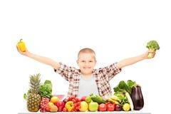 Uma criança entusiasmado que guardam brócolis, e uma pimenta em uma tabela Fotografia de Stock Royalty Free