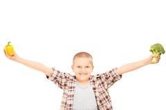 Uma criança entusiasmado que guardaram brócolos, e uma pimenta em sua mão Foto de Stock Royalty Free